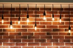 Background Of Brick Wall And Decorative Incandescent Lamps Stock Image