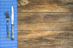 Old silver cutlery with blue and white fabric on rustic wooden table. stock photos