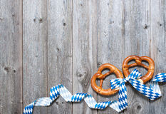 Background for Oktoberfest. Bavarian pretzels with ribbon on wooden board as a background for Oktoberfest stock photo