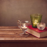 Background with old book and candles on wooden table Stock Image