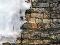 Background old brick wall with big icicle, texture. Vintage Stock Image