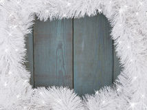 Background of old painted planks and Christmas tinsel. Royalty Free Stock Photography