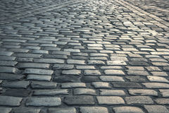Background of old road paved with granite stones Royalty Free Stock Image