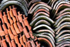 Background. Old roof tiles stacked on a house wall royalty free stock image