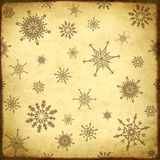 Background of the old, soiled paper and snowflakes pattern Royalty Free Stock Photos