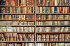 Background of old vintage books on wood bookshelf in a library. Background of old vintage books on wooden bookshelf in a library stock photos