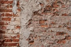 Old vintage dirty brick wall with peeling plaster, background, texture close up. Shabby building facade with damaged plaster. royalty free stock images