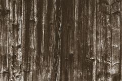 Background from old worn, darkened from time to time, brown knotty vertical wooden plank close up.  stock photo
