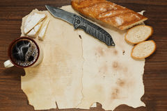 Background of oldened paper sheets with some lunch meals. Old paper sheets on the wooden table with baguette bread, cup of coffee, camembert or brie cheese and a stock photo