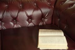 Background is an open old book on a claret-colored leather sofa Royalty Free Stock Images