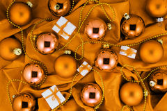 Background of orange Christmas tree balls, little gift boxes and gold decorations on orange silk fabric Royalty Free Stock Photos