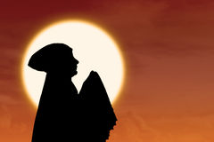 Background of orange sunset silhouette female muslim Stock Photo
