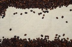 Background from organic spilled coffee arabica in beans with white space for text. Nature cloth linen background Stock Photos
