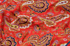 Background of the Paisley shawl. The red cloth with Welsh pears is photographed close-up Stock Photos