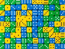 Background pattern of random ordered yellow, green and blue dices stock photography