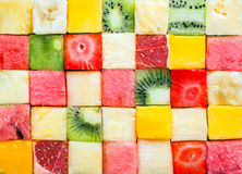 Background pattern and texture of fruit cubes. Seamless background pattern and texture of colourful fresh diced tropical fruit cubes arranged in a geometric Royalty Free Stock Photo