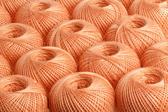 Background peach yarn. Texture of colored yarn skeins stock photos
