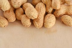 Background with peanuts unpeeled closed up. Background with unpeeled whole peanuts closed up against wooden desk Royalty Free Stock Photos