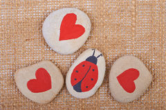 Background of pebbles with hearts and ladybug painted Stock Images