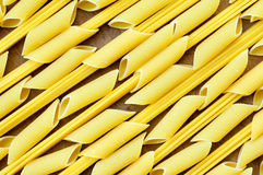 Background of penne and spaghetti on a wooden table.  Royalty Free Stock Images