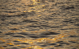 Background photo, sun glare on dark sea water with wave pattern, select focus Stock Photography