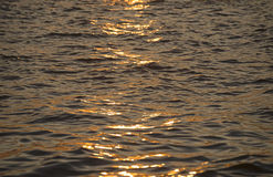 Background photo, sun glare on dark sea water with wave pattern, select focus Stock Photo