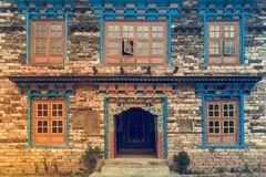 Nepal style windows and door in the old brick wall. Background picture of beautiful woodcarft Nepal style windows and door in the old brick wall. Nepal travel Stock Photo