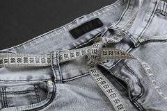 Gray jeans wrapped on a belt with a measuring tape. Background picture, beauty, blue, torso, calorie, care, centimeter, dead end, clothes, clothes, concept royalty free stock images
