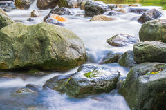 Background Picture of water flows through rocky path of a stream Stock Photos