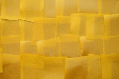 Background of the pieces of tape. Background from small pieces of satin ribbons yellow Royalty Free Stock Photography
