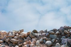 Background from a pile of cobblestones and the sky with clouds royalty free stock image