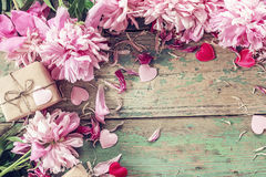 Background with pink peonies, gift box and hearts on old green b Stock Photos