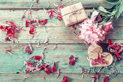 Background with pink peony, peonies petals, gift box and a woode Royalty Free Stock Photography