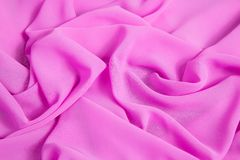 Background of pink soft thin fabric lined with waves. And folds royalty free stock images