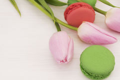 Background with pink tulips and macaroons. Stock Photos