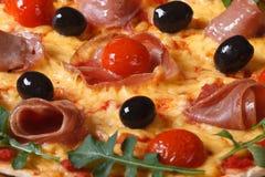 Background of pizza with ham, tomatoes, black olives and arugula. Horizontal macro stock image