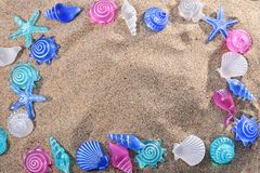 Background with plastic summer motifs. Summer background with seashells and starfish on the beach sand. summer concept Stock Photography