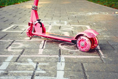 Background of playground with pink little kid scooter and hopsco Stock Photos