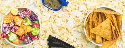 On the background of popcorn two cups with colored caramel corn stock photos