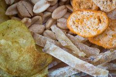 Background of potato chips, fried peanuts, slices of fish and crackers. Texture. close-up. Background of potato chips, fried peanuts, slices of fish and crackers Stock Photos