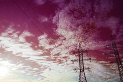 Background of power lines on the background of purple sky and white clouds royalty free stock image