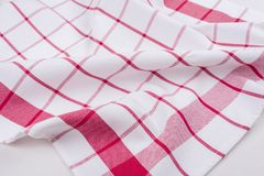 Background for product. Checked tablecloth in red and white cage on textured surface, view from above. Background for product. Checked tablecloth in a red and Stock Image