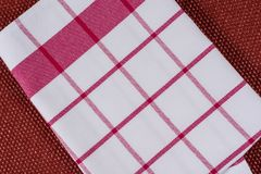 Background for product. Checked tablecloth in red and white cage on textured surface, view from above. Background for product. Checked tablecloth in a red and Royalty Free Stock Images