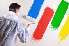 Painter with overals and wall painted with four colors royalty free stock image