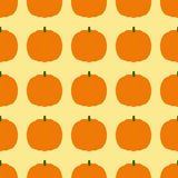 Background with pumpkins. Seamless background with repeating orange pumpkins arranged in straight rows and isolated on ginger background. Ideal for holiday Stock Images