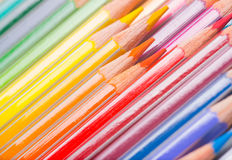 Background of rainbow coloured pencils. Background of rainbow coloured wooden pencil crayons arranged diagonally with a close up view of the tips Royalty Free Stock Photos