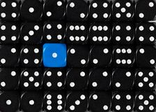 Background of random ordered black dices with one blue cube. Pattern background of random ordered black dices with one blue cube stock photography