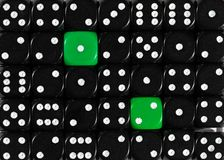 Background of random ordered black dices with two green cubes. Pattern background of random ordered black dices with two green cubes royalty free stock photography