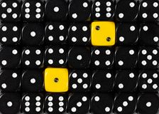 Background of random ordered black dices with two yellow cubes. Pattern background of random ordered black dices with two yellow cubes stock photos