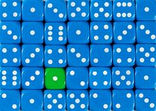 Background of random ordered blue dices with one green cube. Pattern background of random ordered blue dices with one green cube royalty free stock photo